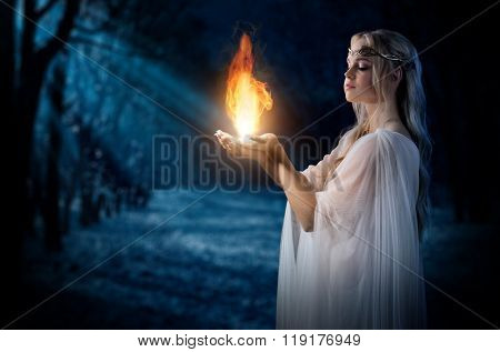 Young elven girl holding fire in palms at night forest