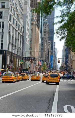 NEW YORK - CIRCA SEPTEMBER 2015: Throng of Yellow Taxi Cabs Stopped at Red Light at Intersection on Busy Street in Manhattan, New York City, New York, USA