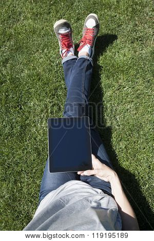 Cross Legs On Grass With Tablet
