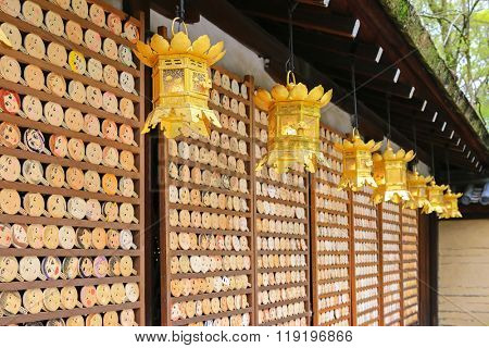 Shallow depth of field of beautiful golden lanterns hanging  in front of mirror-shaped wooden preyer tablets (called Kagami ema) at Kawai-jinja Shrine, in Kyoto, Japan