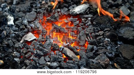 Close-up of embers. Orange burning coals inside a barbecue grill.