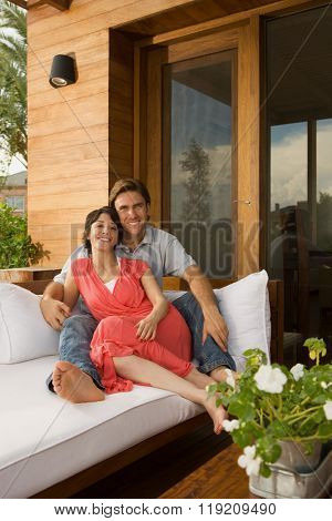 Couple relaxing on sofa outdoors