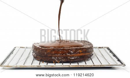 Closeup Of Chocolate Icing Pouring Over Sacher Torte Towards White