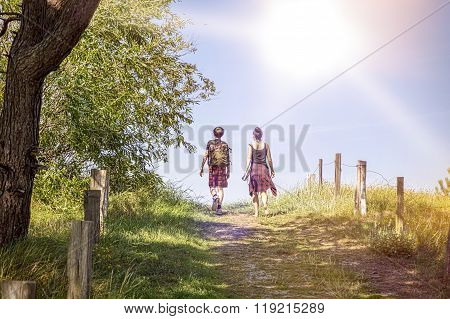 Two Teenager Walking A Path At Noon