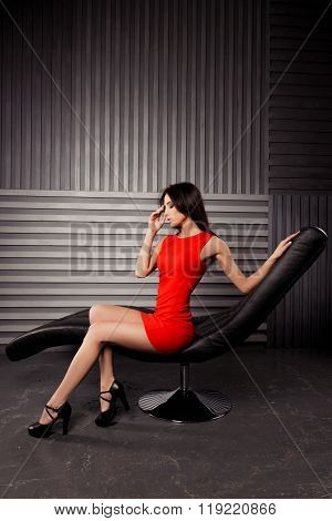 Seductive Brunette In Red Dress Sitting On Black Chair