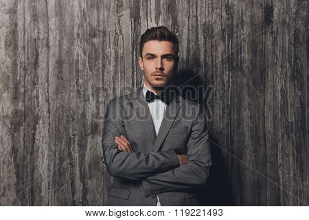 Handome Rigid Man With Bow-tie In Suit On The Grey Background Crossing Hands