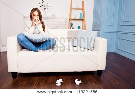 Sick  Girl With Fever Sneezing In Tissue Sitting On Sofa