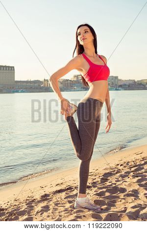Attractive Slim Girl Stretching Her Legs Near The River