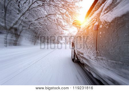 Car And Falling Snow In Winter On Forest Road With Much Snow.(motion Blur)