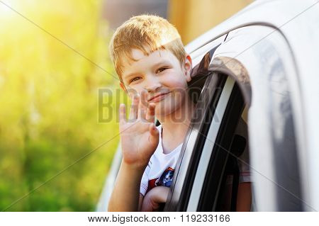 Child Leaned Out The Window Of A Car And Waving His Hand.