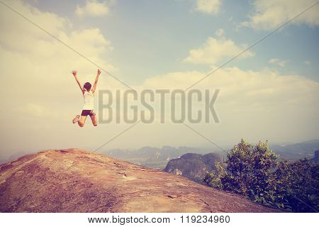 young successful woman jump on mountain peak rock