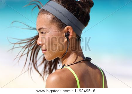 Fitness girl with sport in-ear wireless headphones. Asian female athlete woman runner wearing Bluetooth earphones with wing tip design for sports activities. Portrait closeup.