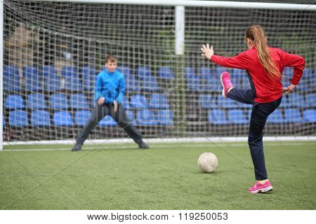 Girl in a red tracksuit throws the ball into the goal with boy keeper