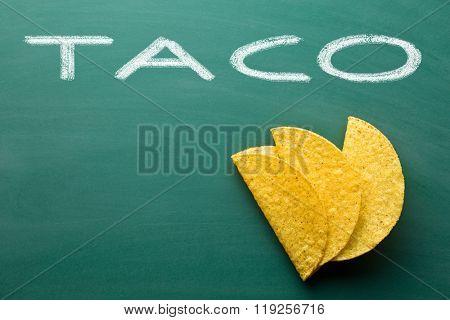 crispy taco shells on green chalkboard