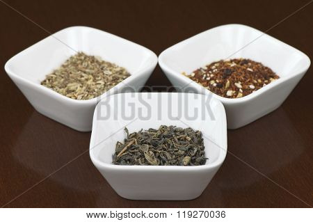 Dry tea leaves in square bowls