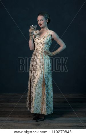Chique Vintage 50S Fashion Woman In Gold Dress Holding Champagne Glass.