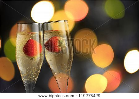 Closeup of stylish champagne flutes filled with chilled bubbly and a floating strawberries for celebrating a romantic evening together