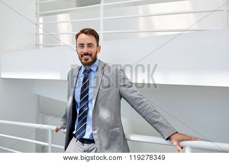 Young male boss smiling for camera while resting after successful meeting with international partner