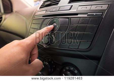 Hand Pushing The Power Button To Turn On The Car Stereo System