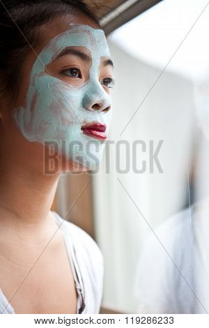 Young cute girl with a self made beauty mask