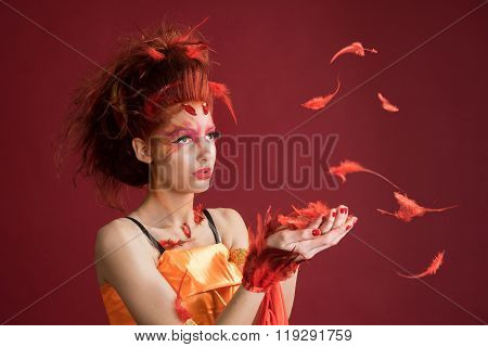 Phoenix. Young girl portrait and flying feathers. Woman holds a feather in hands.