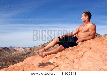 Athletic young man on red rocks