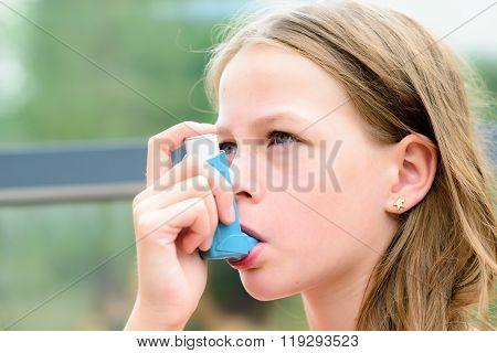 Girl Having Asthma Using The Asthma Inhaler