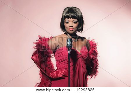 Retro 60S Female African Soul Singer In Red Dress Against Pink Background.