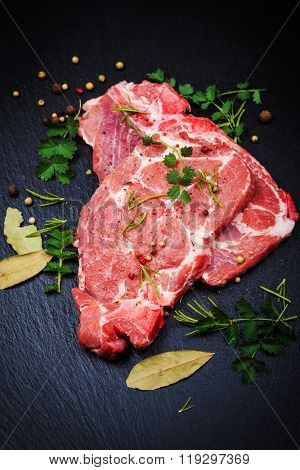 Fresh raw pork meat on black board with spices and herbs