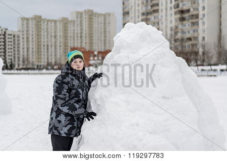 Teen Boy Standing At Makeshift Snow Fort
