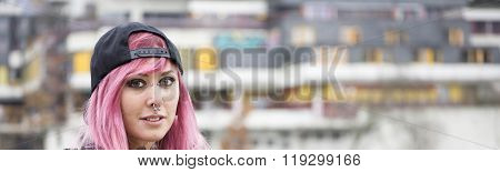 woman with piercings and pink hair at housing estate