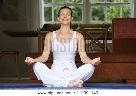 Woman Sitting On Floor In Yoga Position At Home