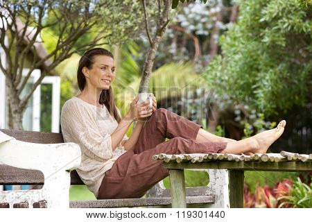 Woman Sitting Outside With Cup Of Coffee