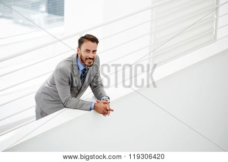 Smiling young businessman dressed in classic suit resting after conference