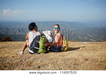 Man and woman with a rucksack on back sitting with map on high mountain hill against beautiful view