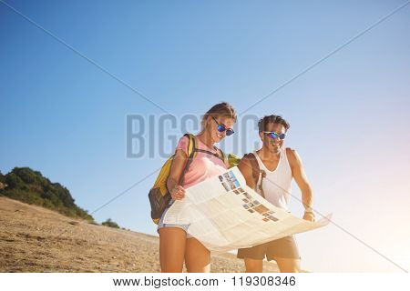 Two cheerful travelers holding map while standing on a high hill against blue sky in sunny day