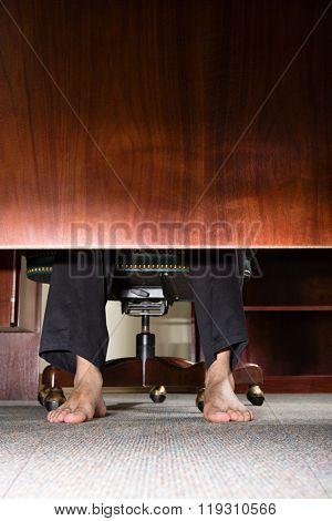 Feet of businessman under desk
