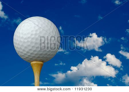 Golf Ball & Tee with clouds and sky background.