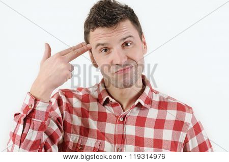 Young Emotional Woman With A Finger To Her Temple Like A Gun  On White Background