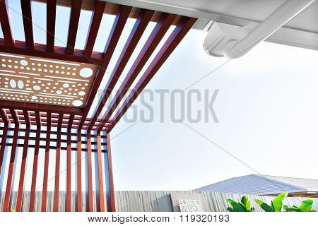 Low Angle View Of Wooden Pillars And Beams With A White Carving Attached To It.