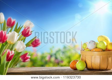 Easter eggs in the basket on wooden boards