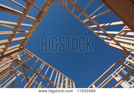 New residential construction home framing against a deep blue sky.