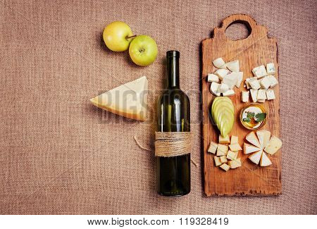 Cheese Platter Garnished With Honey, Apple And Bottle Of Wine On Rustic Wooden Board