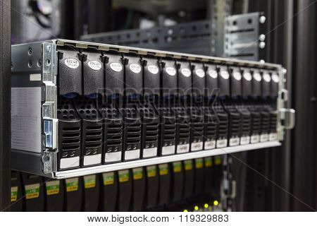 IT Engineer installs equipment in the rack in datacenter poster