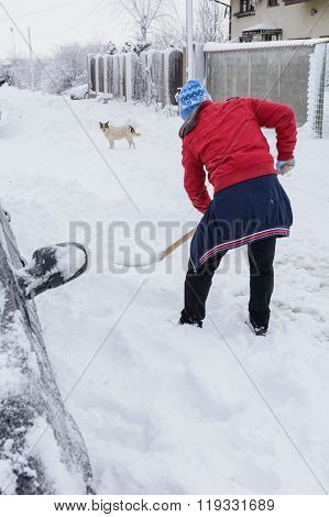 Man Cleans Road After A Big Snowstorm. Man Digging Snow With Shovel Near Car After A Big Snowstorm..