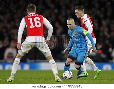 LONDON, ENGLAND - FEBRUARY 23: Andres Iniesta of Barcelona runs at Aaron Ramsey of Arsenal during the Champions League match between Arsenal and Barcelona at The Emirates Stadium