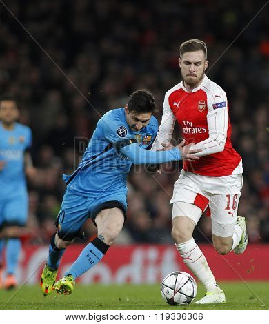 LONDON, ENGLAND - FEBRUARY 23: Lionel Messi of Barcelona and Aaron Ramsey of Arsenal compete for the ball during the Champions League match between Arsenal and Barcelona at The Emirates Stadium