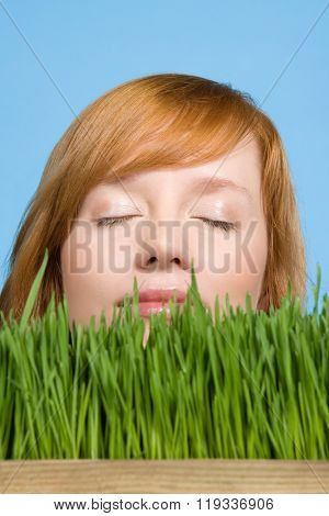 Woman smelling grass poster