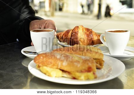 man sitting in a table in the terrace of a cafe set for breakfast, with some cups of coffee, a croissant and a spanish omelette sandwich