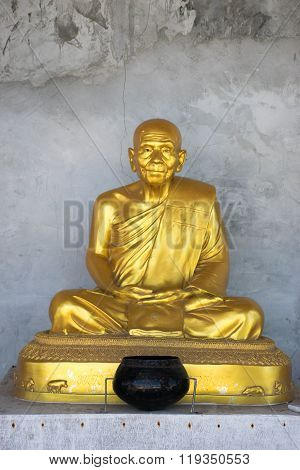 Bronze statue of sitting monk with grey concrete background